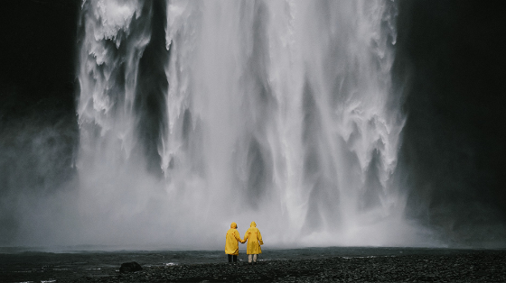 Picture of waterfall, two people in yellow raincoats