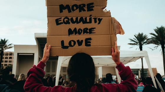 """Demonstrator with a cardboard with the text  """"MORE EQUALITY MORE LOVE"""""""